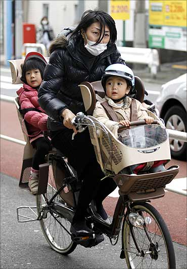 A woman and her children ride on a bicycle past a ward office in Tokyo.
