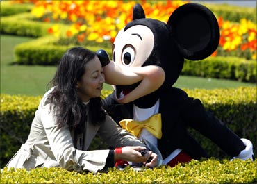 A visitor is kissed by Disney character Mickey Mouse at Tokyo Disneyland.
