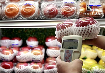 A Taipei City health official shows the media the radiation reading of Japanese imported apples.