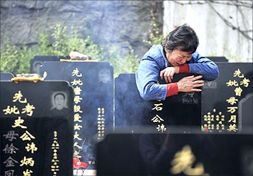 A woman cries as she hugs the tombstone of her husband at a public cemetery.