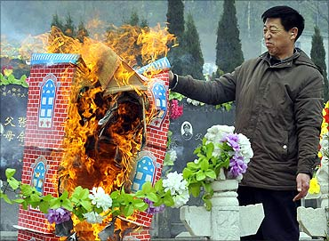 A man reacts as he burns a paper villa as an offering in front of tombstones of his ancestors.