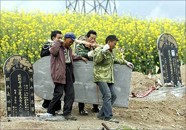 Workers carry a tombstone at a public cemetery.
