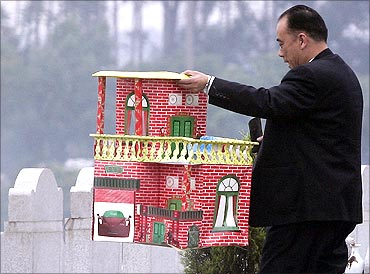 A man holds a paper house as he prepares to burn it as an offering to his ancestors at a cemetery.
