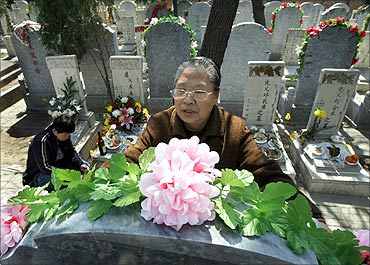 A woman places flowers on the tomb of a relative at Babao Cemetery in Beijing.