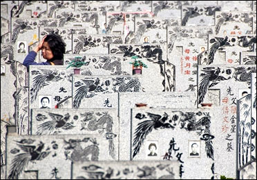 A Chinese woman walks among tombstones at Songhe graveyard in Shanghai.