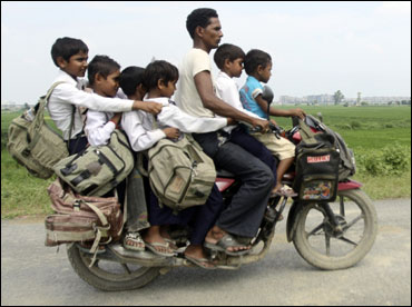 A man rides a motorcycle carrying six children on their way back home from school at Greater Noida.