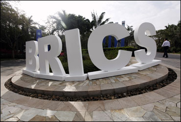 A man walks past a signage decoration for the BRICS summit.