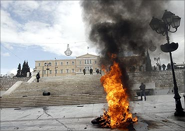 A police motorcycle is on flames in front of the parliament during riots in Athens.