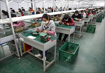 Employees work on circuit boards at a workshop of an energy-saving lighting device factory.