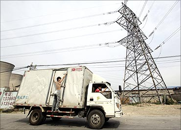 A truck carrying a man drives past electricity wires near a coal-fired power plant.