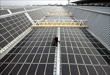 Workers work on a set of solar panels on the rooftop of the Nanjing South Railway Station Nanjing.