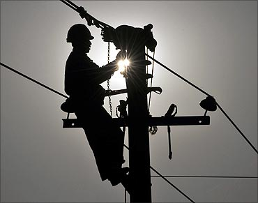 worker repairs an utility pole on the outskirts of Yingtan.