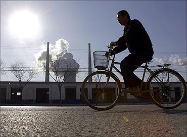 A chimney billows smoke from a coal-burning power station behind a workman riding a bicycle.