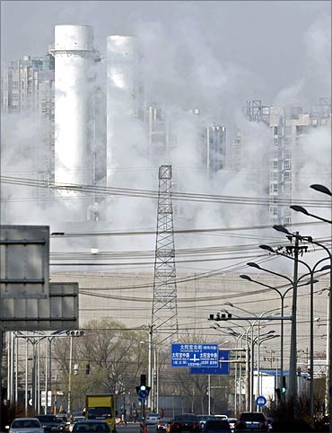 Chimneys and buildings are seen through thick steam at Taiyanggong Gas-fired Thermal Power Station.