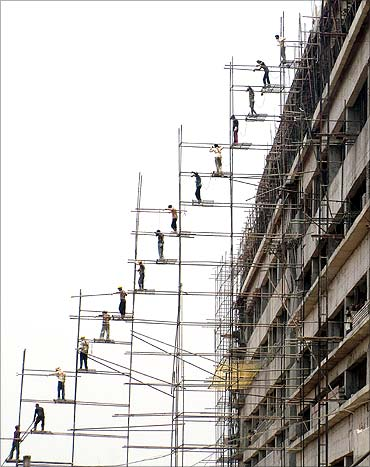 Labourers work at the construction site of a commercial complex.