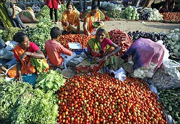 Vendors sell their vegetables at an open air fruit and vegetable market.