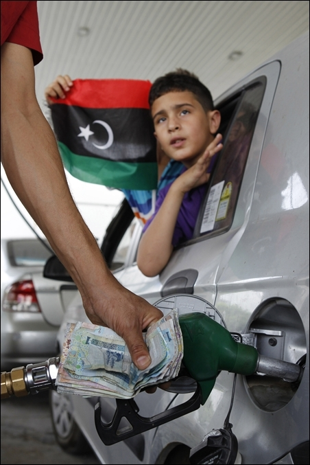 A man fills up the tank of a car at a petrol station in Tripoli.