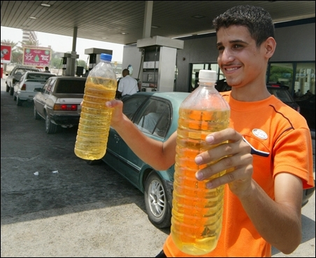 A Bahraini youth sells bottles of petrol to queuing motorists in Manama.