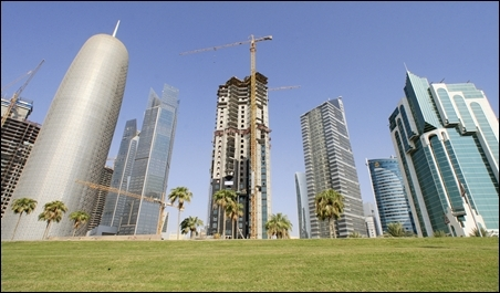 The Doha Office Tower (L) stands next to skyscrapers under construction in Doha.