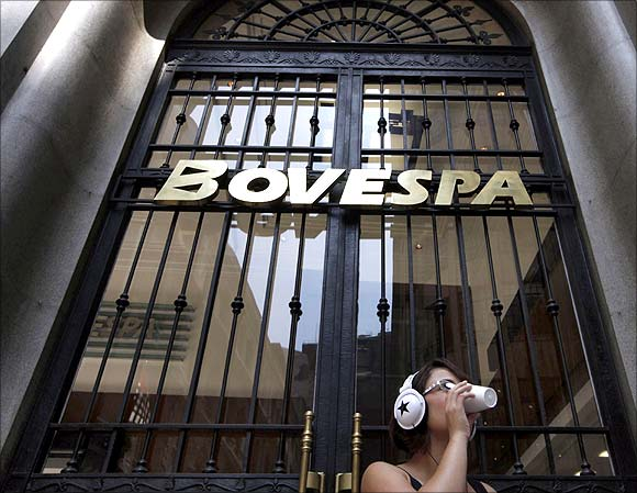 A woman drinks coffee in front of the stock exchange in Sao Paulo.