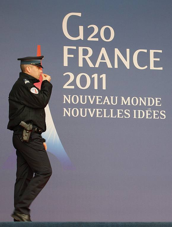 A French police officer walks past the G20 logo and slogan outside the festival palace as preparations for the G20 summit continue in Cannes