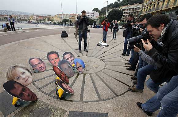 Photographers take photo of masks showing G20 leaders during an anti G20 demonstration to protest against globalisation in Nice