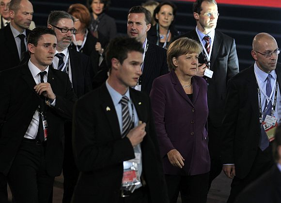 Germany's Chancellor Angela Merkel is surrounded by security as she walks at the G20 venue where world leaders gather in Cannes