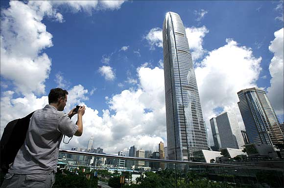 A visitor takes a picture in front of Two IFC, Hong Kong's highest commercial building, on a sunny day.