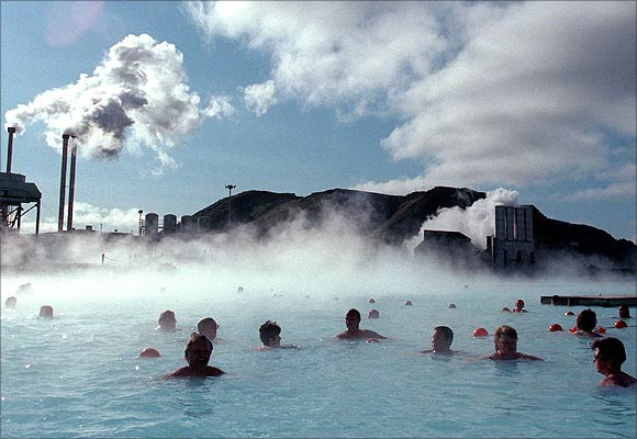 Bathers at the Blue Lagoon hot springs swim in hot mineral waters amid a chilly wind as a thermal electricity plant looms in the background.