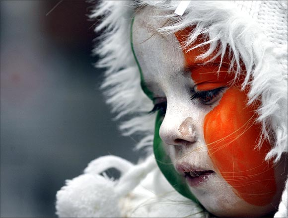 A girl with face paint in Irish national colours looks on during the Saint Patrick's Day parade along Dublin's city centre.