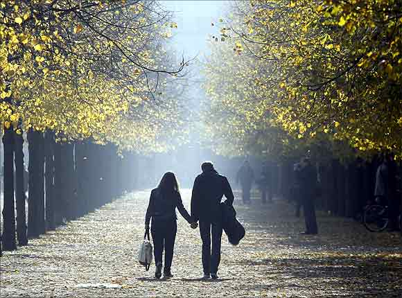 People walk in an allee near the Brandenburg Gate during a sunny day in Berlin.