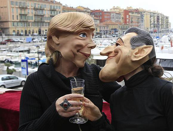 Anti G20 demonstrators wearing masks of Germany's Chancellor Angela Merkel (L) and France's President Nicolas Sarkozy take part in an action against globalisation in Nice.
