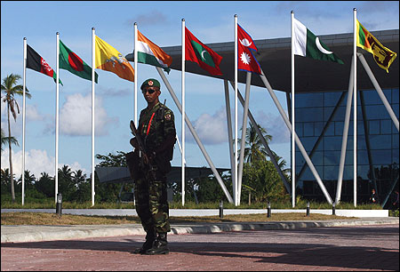 A Maldives army soldier stands guard near the flags of the SAARC countries in Addu.