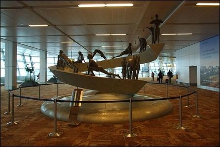 Sculpture at T3 terminal depicting twelve asana's of the Surya Namaskar.
