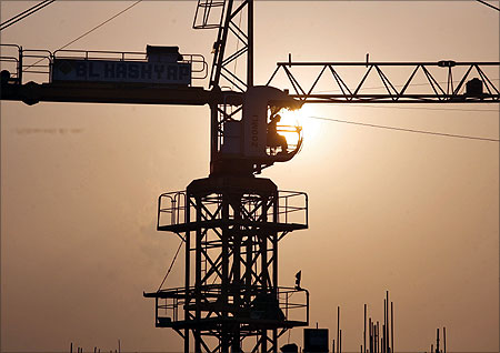 A worker sits inside a crane is silhouetted against the setting sun at the construction site of a commercial complex in Noida.