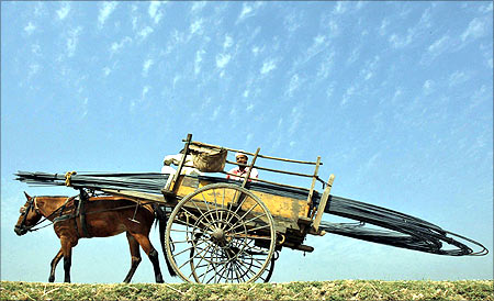 People transport iron rods on a horsecart to a construction site of a residential complex on the outskirts of Jammu.