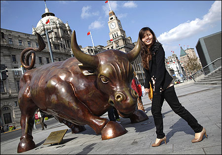 A woman poses next to a bull statue known as the Bund Financial Bull along the Huangpu River in Shanghai.