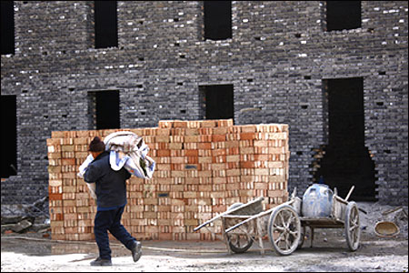 A worker carries blankets as he walks in front of a block of apartments under construction in Beijing.