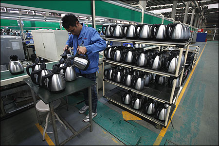 A Galanz employee tests electric kettles at a production line in a factory in Zhongshan.