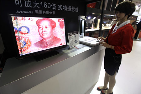 An employee operates a camera to zoom in on the image of a Chinese one-hundred yuan banknote.