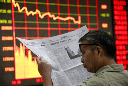 An investor reads a newspaper in front of an electrical board showing stock information at a brokerage house in Huaibei.