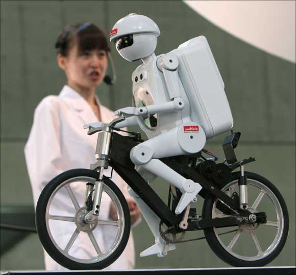 Humanoid robot Seisaku-kun pedals a bicycle during a demonstration at the Combined Exhibition of Advanced Technologies (CEATEC) in Makuhari, northeast of Tokyo.