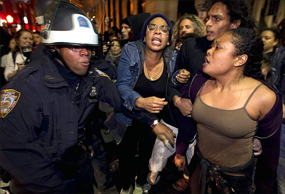 Sade Adona (R) yells as fellow members of the Occupy Wall Street movement clash with New York Police Department officers after being removed from Zuccotti Park in New York.