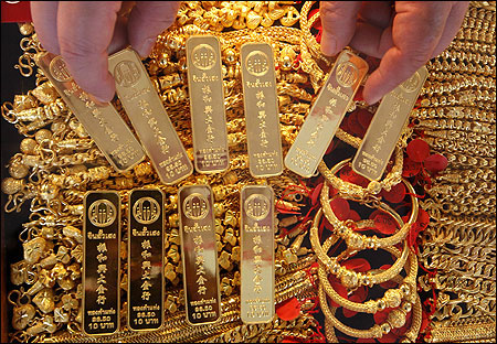 A shopkeeper shows gold bars in Bangkok's Chinatown.