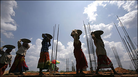 Women labourers work at the construction site of a commercial complex.