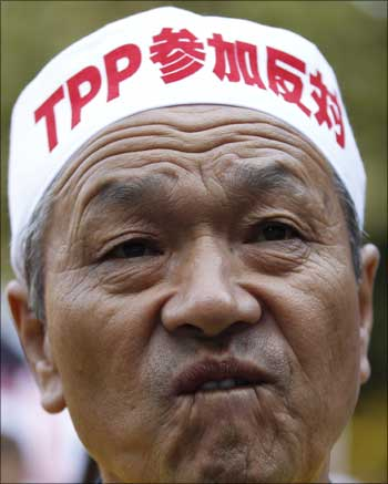 A farmer attends a rally as he wears a sign reading 'against participating in TPP' in Tokyo.