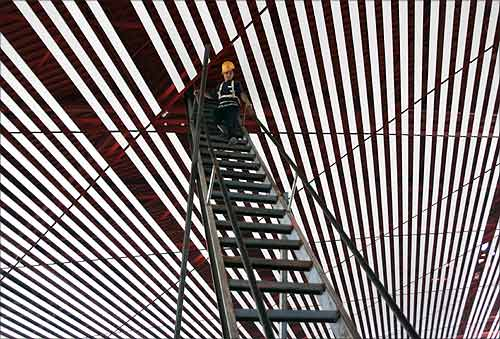 A worker walks downs a ladder from the roof of the new terminal of Beijing's International Airport.