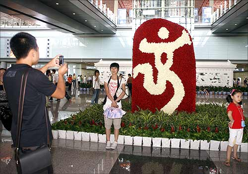 Travellers pose near a Beijing Olympic emblem at Beijing airport.