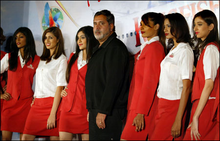 Mallya (C) poses with air stewardesses during the launch of Kingfisher Airlines.