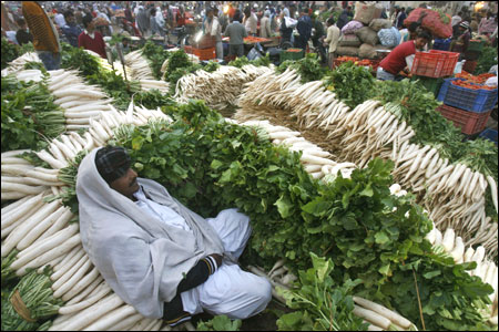 A vendor sits among piles of radishes at a wholesale vegetable market in Chandigarh.